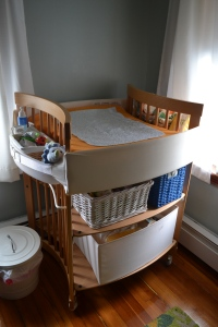 most changing tables have the baby perpendicular to you, but this one is different as you can see.  It usually comes with two canvas doors.  I cheaped out and got only one of the drawers and used baskets on the top shelf.